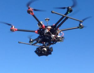 Multi-rotor drone carrying a full-size HD camera for aerial photography and videography